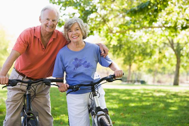 elderly couple smiling on bikes