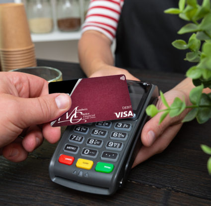 Image shows default debit card making purchase via contactless-enabled device