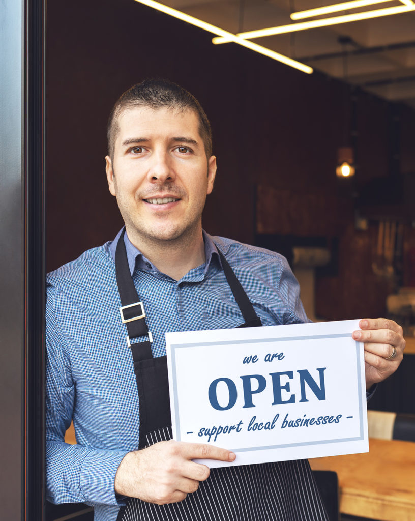Business owner holding open sign