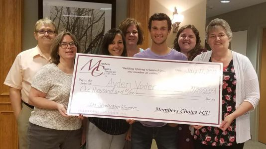 Scholarship Winner, Ayden Yoder, with staff and large check